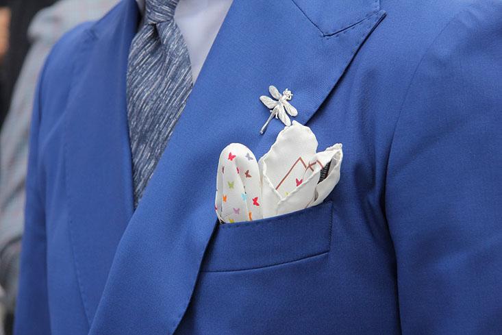 Delikatny, drukowany jedwab i ręcznie obrębione krawędzie – poszetkowy ideał. Do stylizacji opartych na ciemnym garniturze i białej koszuli, idealna będzie jednak biała lniana poszetka, równo złożona i wystająca 1 – 2 cm ponad krawędź brustaszy.